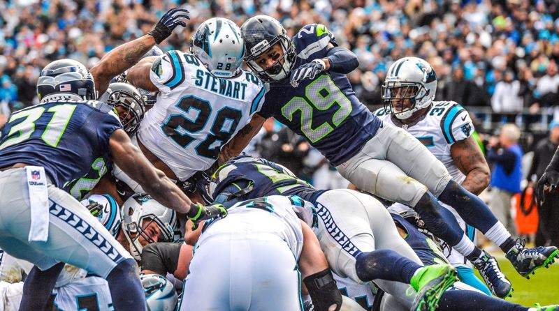 TRIBUNE PHOTO: MICHAEL WORKMAN - Jonathan Stewart of the Carolina Panthers goes over the top of the Seattle defense to score in Sunday's NFL playoff game.
