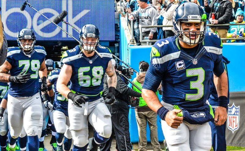 Quarterback Russell Wilson (right) leads Seahawks teammates Garry Gilliam (left) and Justin Britt onto the field.