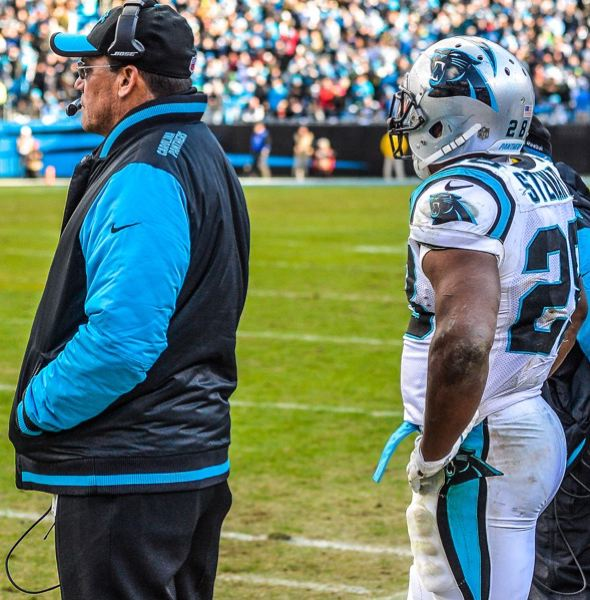 Carolina running back Jonathan Stewart (right) stands behind coach Ron Rivera, waiting the call to go back in on offense.