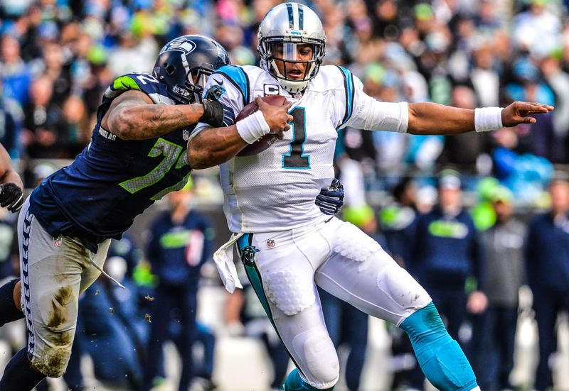 Seattle defensive end Michael Bennett (left) gets to Carolina QB Cam Newton.