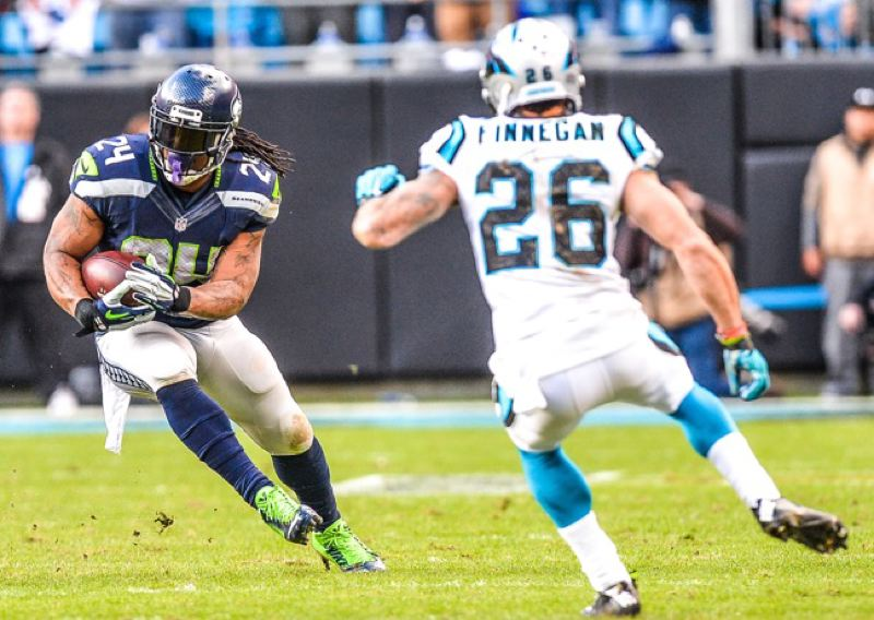 Seattle running back Marshawn Lynch (left) makes a cut, as Cortland Finnegan defends for Carolina.