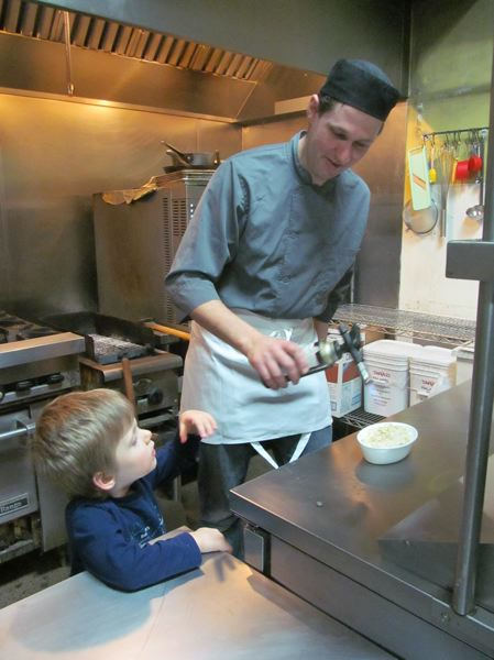 PHOTOS BY DICK TRTEK - Co-owner of Mezza, Joris Barbaray, fires up the blowtorch to finish off a creme brulee, while his son, Tristan, watches.