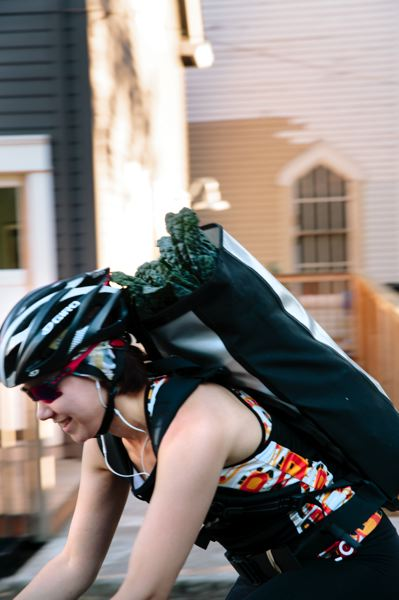 COURTESY PHOTO: LAURA JENNINGS - A cyclist heads off with a bag of veggies picked up from Door of Hope church last year.