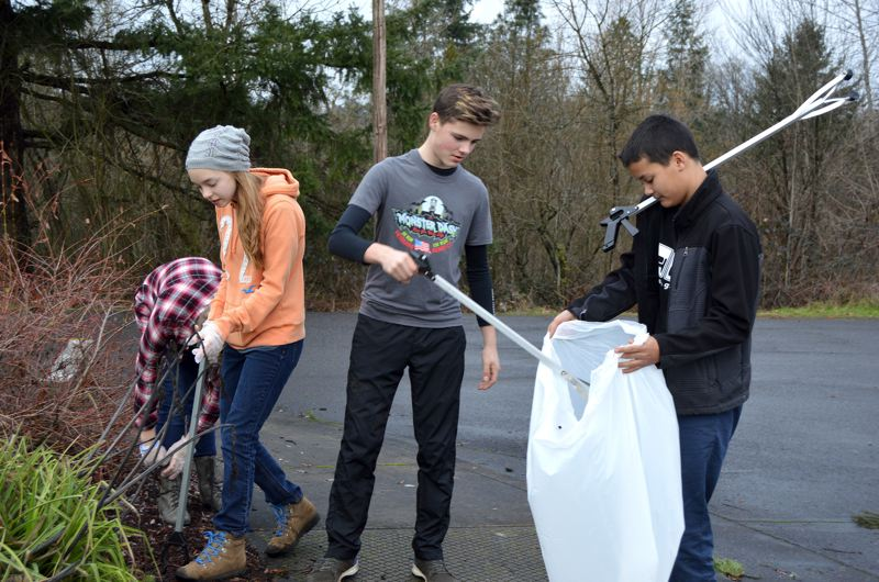 SPOTLIGHT PHOTO: NICOLE THILL - A group of eighth-grade students, Alana Saul, Maggie Wheeldon, Corbin Edson and Alex Bilton, pick up trash in the parking lot of the middle school. A group of students, parents, and staff, including school Principal Carol Dowsett, picked up litter around the school grounds and wetland areas.