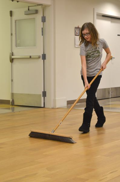 SPOTLIGHT PHOTO: NICOLE THILL - Lillian Janke, a fifth-grader, helps sweep the dance floor in the St. Helens Senior Center. Lillian Janke volunteered to help her father, Mark Janke, St. Helens Middle School dean of students, on Monday, Jan. 18.