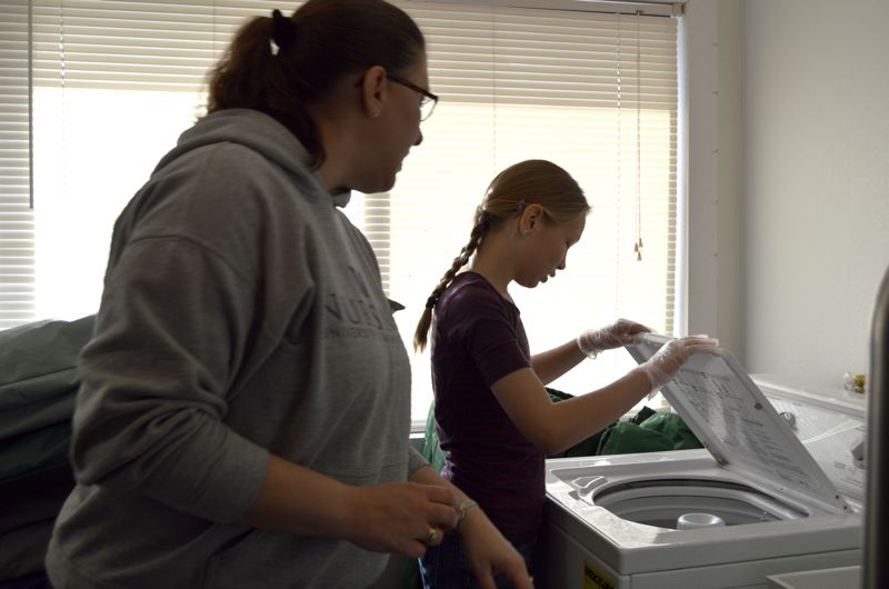 SPOTLIGHT PHOTO: NICOLE THILL - Danielle Nelson and her daughter, Kathryn Nelson, a fifth-grader, help wash a load of laundry at the Community Action Team building on Monday. Danielle's son, Jakob Nelson, an eighth-grader, also helped with various tasks at the Warming Center on Monday, including counting donations and organizing supplies.