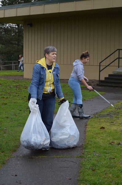 SPOTLIGHT PHOTO: NICOLE THILL - Carol Dowsett, the St. Helens Middle School Principal, carries bags of trash collected from the school grounds on Monday. Students found everything from scooters to tires to garden shears while cleaning up the area around the school on N 16th Street and West Street.