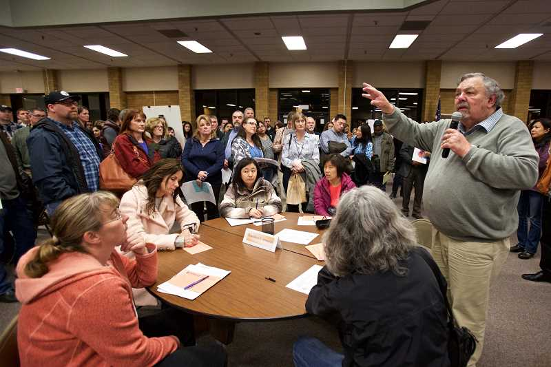 TIMES PHOTO: JAIME VALDEZ - Dick Withycombe, hired by the Beaverton School District to facilitate boundary changes, discusses the process with parents and other visitors during the open house.