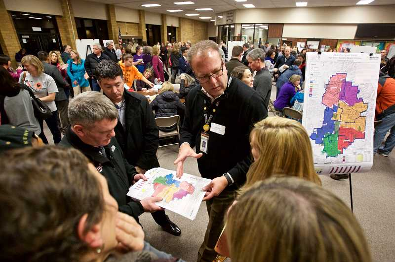 TIMES PHOTO: JAIME VALDEZ - Beaverton School District Deputy Superintendent Carl Mead (center) talks about proposed attendance areas with a small group of people during the open house.