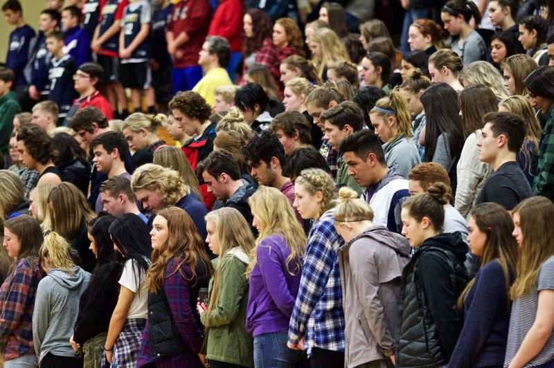 TRIBUNE PHOTO: JAIME VALDEZ - Canby High students and others observe a moment of silence in honor of graduate AJ Schlatter before Friday night's boys basketball game at home against Lake Oswego.