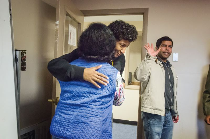 TRIBUNE PHOTO: JONATHAN HOUSE - Abdul Sheikh, a junior at Madison High School and a refugee from Somalia, hugs Immigrant & Refugee Community Organization Youth Program coordinator Abinnet Haile. Tommy Rodrigues, right, is Sheikh's mentor but the Refugee/Immigrant Mentoring program is sorely in need of more male mentors.