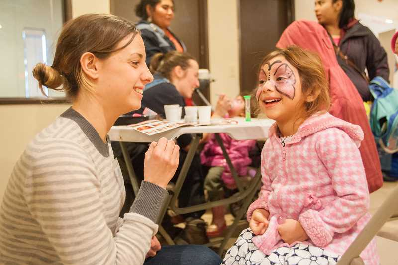 OUTLOOK PHOTO: JOSH KULLA - Courtney Kucera, a volunteer with Wallace Medical Concerns, enjoys a face-painting session Tuesday at a free clinic put on at the Human Solutions Winter Family Shelter.