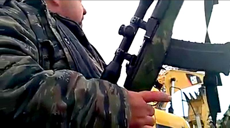 COURTESY PHOTO - A screenshot from the Defend Your Base live YouTube broadcast shows an armed miltant preparing a defensive position near the edge of the Malheur National Wildlife Refuge compound. Several militants stayed on the compound after arrests of the occupation's leaders Tuesday evening.