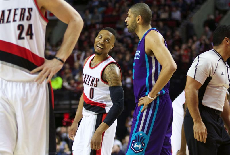 TRIBUNE PHOTO: JAIME VALDEZ - Damian Lillard gives a look to former teammate Nicolas Batum after scoring a basket and drawing a foul on Batum in the Trail Blazers' victory Friday night over the Charlotte Hornets.