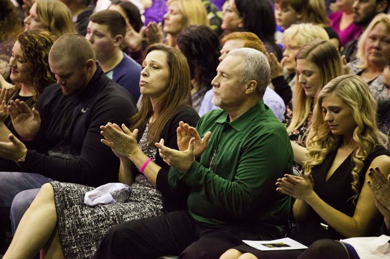 TRIBUNE PHOTO: ADAM WICKHAM - The Schlatter family applauds during remarks Sunday at Stott Center.