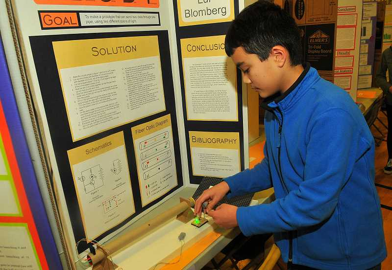 SPOKESMAN PHOTO: VERN UYETAKE - Lui Blomberg, Wood seventh-grader, shows how fiber optic cables work.