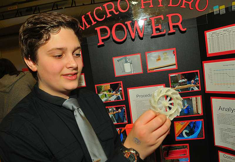 SPOKESMAN PHOTO: VERN UYETAKE - Wood seventh-grader Michael Culp demonstrates his micro water power project.