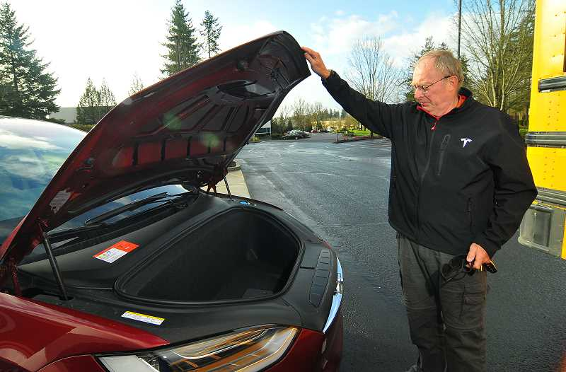 SPOKESMAN PHOTO: VERN UYETAKE - John Schenk opens the front trunk -- or 'frunk' -- of his Tesla Model X.