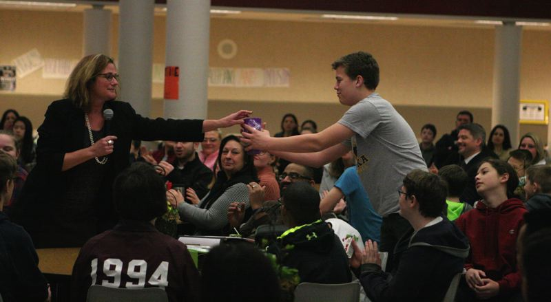 TIMES PHOTO: MARK MILLER - Lisa Knodle-Bragiel, director of admissions at Linfield College, gives Hazelbrook Middle School student Josh Lakeman a Linfield cup and a cookie for answering a question during Hazelbrook's 'Respectful Celebration.'