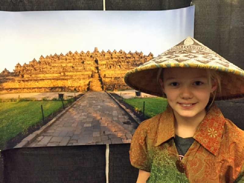 SUBMITTED PHOTO: BRENDA BALLEW - Lake Grove third-grader Berit Ballew wears a traditional Indonesian hat and dress while standing in front of a poster of a ninth-century Buddhist temple, Borobudur.