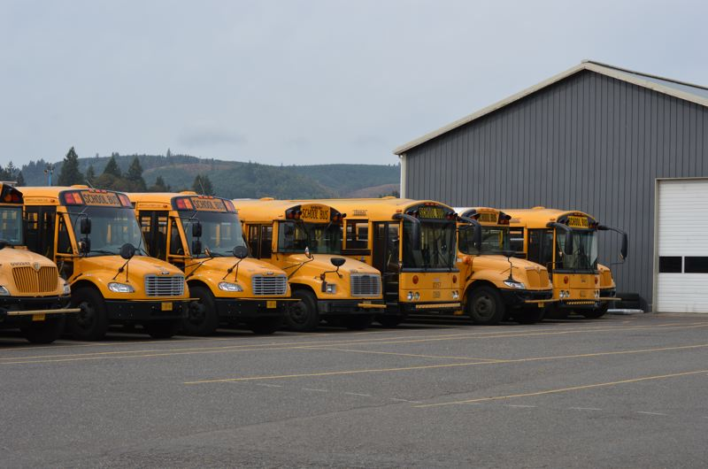 SPOTLIGHT PHOTO: NICOLE THILL - A row of buses sits outside the garage of the First Student garage in Scappoose off Highway 30. The Scappoose School District will not renew its contract with First Student after 35 years of service with the bus company.