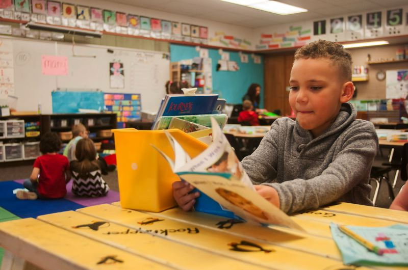 OUTLOOK PHOTO: JOSH KULLA - Powell Valley Elementary kindergarten student Reece Mosley reads a book Thursday in teacher Melissa Castellanos classroom. A recent Oregon Department of Education study suggests that east Multnomah County children are not as kindergarten-ready as their peers in other parts of Oregon.