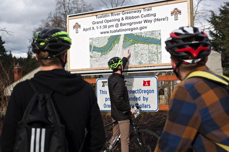 TIMES PHOTO: JAIME VALDEZ - Nick Levee of Lake Oswego shows his buddies, Joe Lukens, left, and Zack Proffitt where they traveled along the Tualatin River Greenway Trail on Monday.