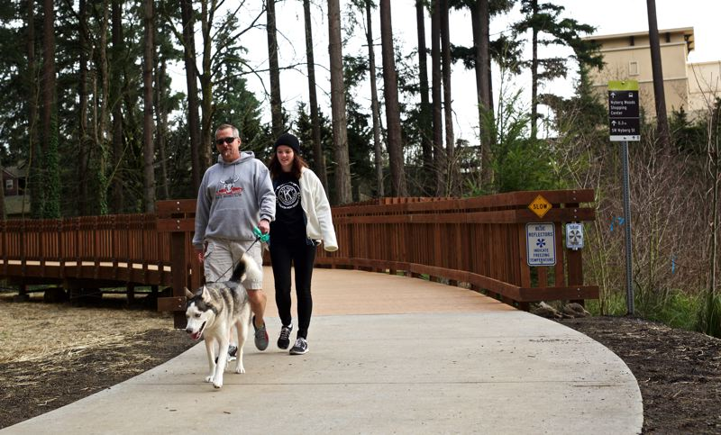 TIMES PHOTO: JAIME VALDEZ - Gregg Webber, left, and his daughter Denali come down the ramp that links the Nyberg Woods shopping center with a new segment of the Tualatin River Greenway Trail.