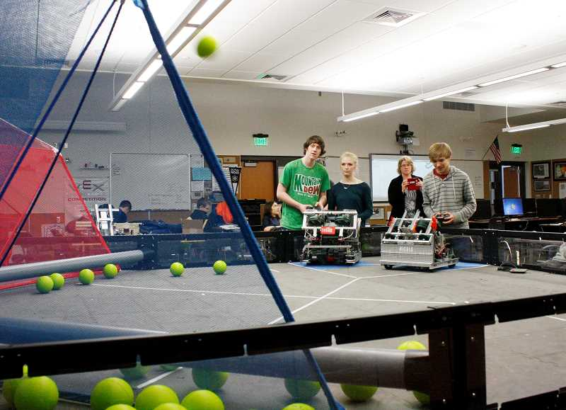 POST PHOTO: ELIZABETH WENDT KELLAR - Robotics Club team members test their robots tossing abilities at an after-school club meeting. Sandy HIgh School will host the VEX Robotics Competition Oregon State Championship Feb. 27-28.