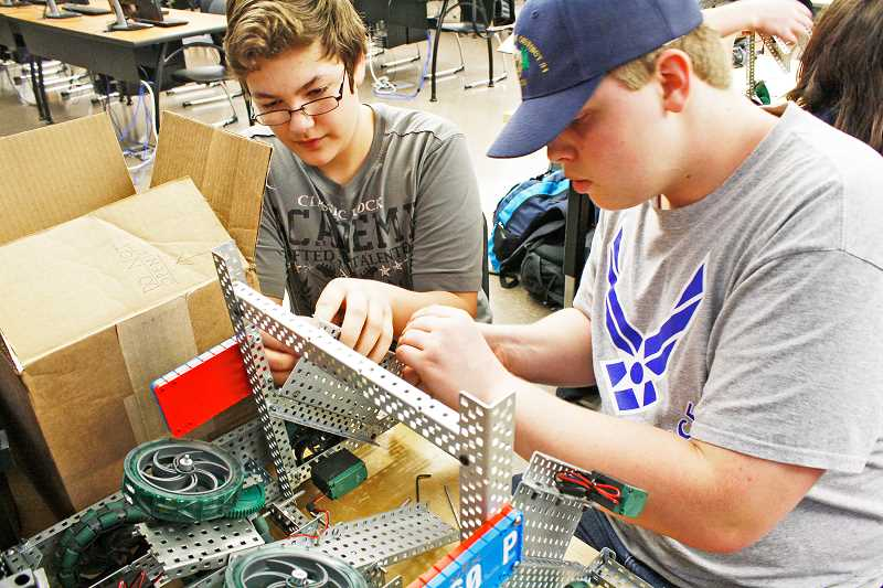 POST PHOTO: ELIZABETH WENDT KELLAR - Sandy High School Robotics Club members and freshmen Tyler Routh, 14, and Jacob Syle, 15, work on their robots at an after school meeting of the club.
