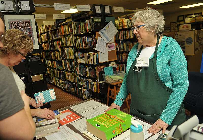 REVIEW PHOTO: VERN UYETAKE - Volunteer Barbara Gold helps customers find exactly what they want at Booktique.