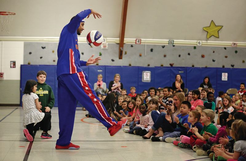 TIMES PHOTO: JONATHAN HOUSE - Julian Zeus McClurkin of the Harlem Globetrotters impresses the assembly at Fir Grove Elementary, during a talk on anti-bullying.