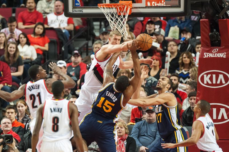TRIBUNE PHOTO: JOSH KULLA - Mason Plumlee rejects a shot by Derrick Favors in the Trail Blazers' 115-111 win at home Sunday over the Utah Jazz.