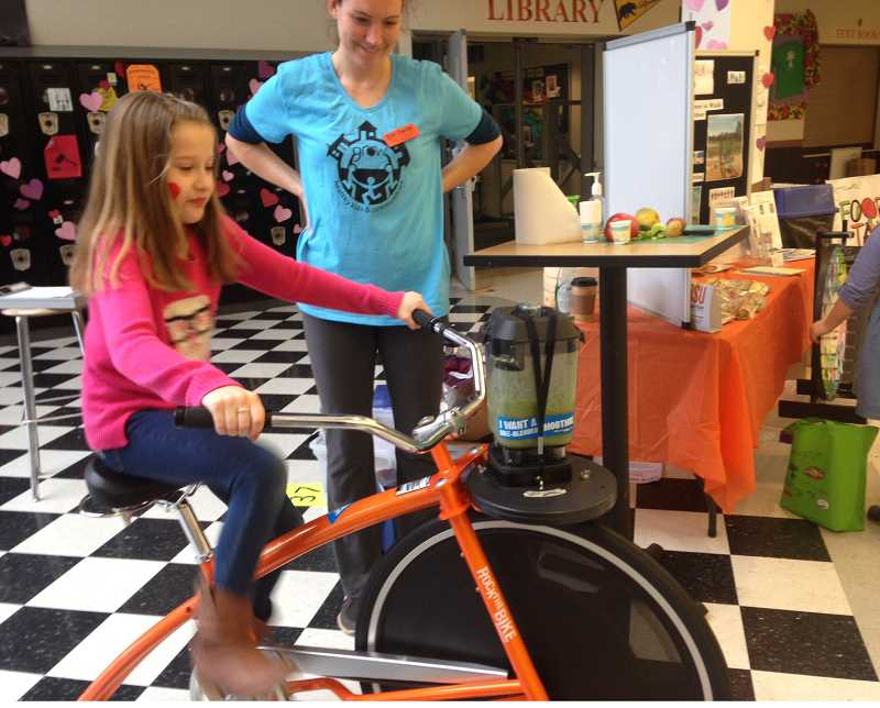 PEGGY SAVAGE - Erin Devlin, with GROW Healthy Kids & Communities, a OSU Extension service in Molalla and Clackamas County, got kids to try out the 'Bike Blender' making smoothies at her booth during the 2015 Farmers Fair in Molalla.