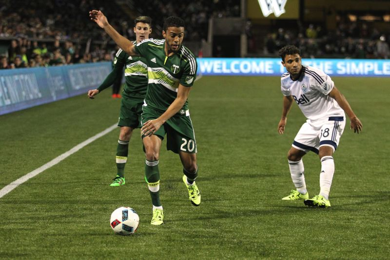 TRIBUNE PHOTO: JAIME VALDEZ - Portland Timbers defender Taylor Peay (20) runs past Vancouver Whitecaps midfielder Kianz Froese (right).