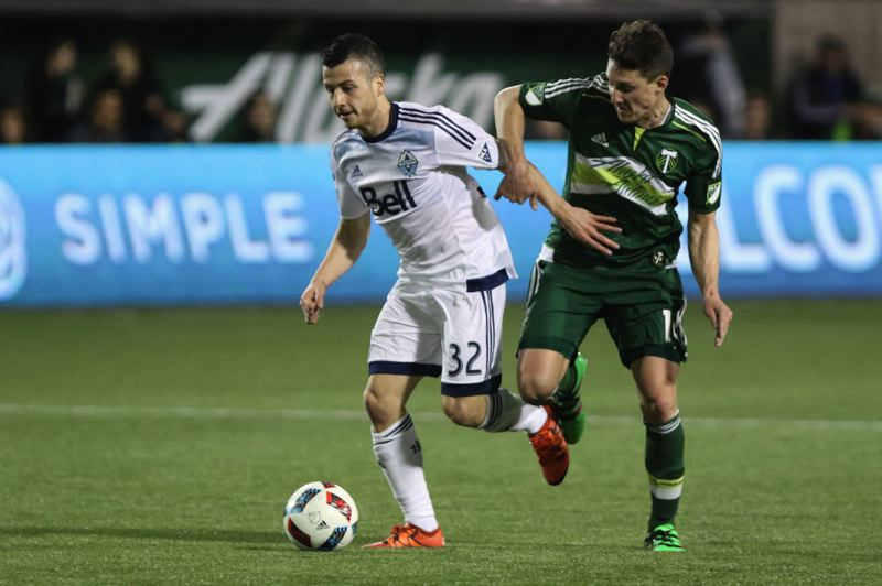 TRIBUNE PHOTO: JAIME VALDEZ - Vancouver Whitecaps midfielder Marcos Bustos (left) battles for the ball with Portland Timbers midfielder Ben Zemanski at Providence Park.