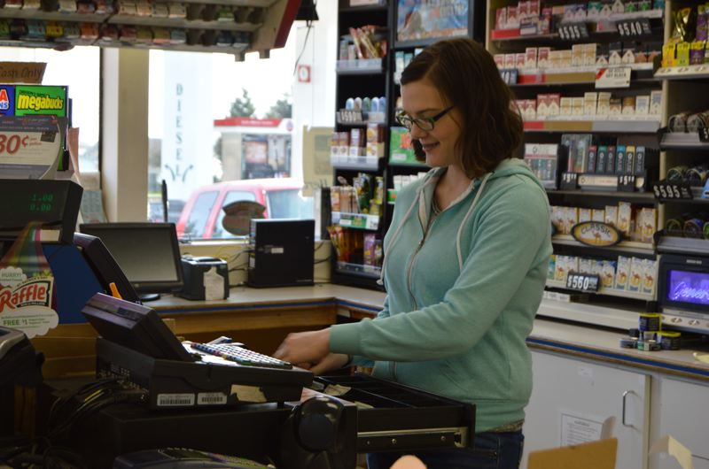 SPOTLIGHT PHOTO: COURTNEY VAUGHN - Kimberly Williamson rings a customer's purchase at Jackpot Market in Scappoose. The market employs several part-time, minimum-wage employees who could see their hourly wages increase, starting this July.