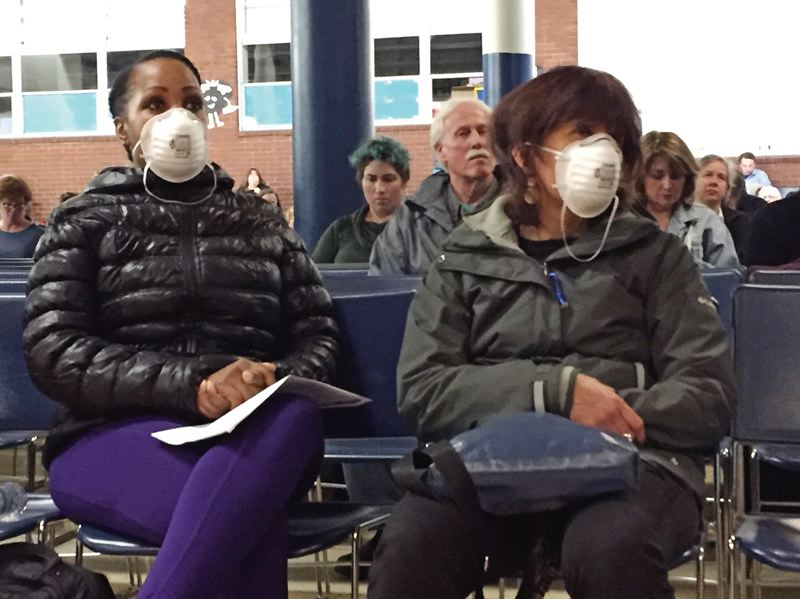 PHOTO COURTESY OF CASSANDRA PROFITA, OPB/EARTHFIX - Two residents wore extra protection at a recent community meeting to discuss toxic levels of metals detected in the air in Southeast Portland.