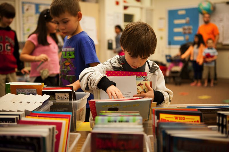 OUTLOOK PHOTO: ADAM WICKHAM  - Kindergartner Elijah Berry carefully selects a book after winning the book walk at the Butler Creek Elementary School family literacy night.