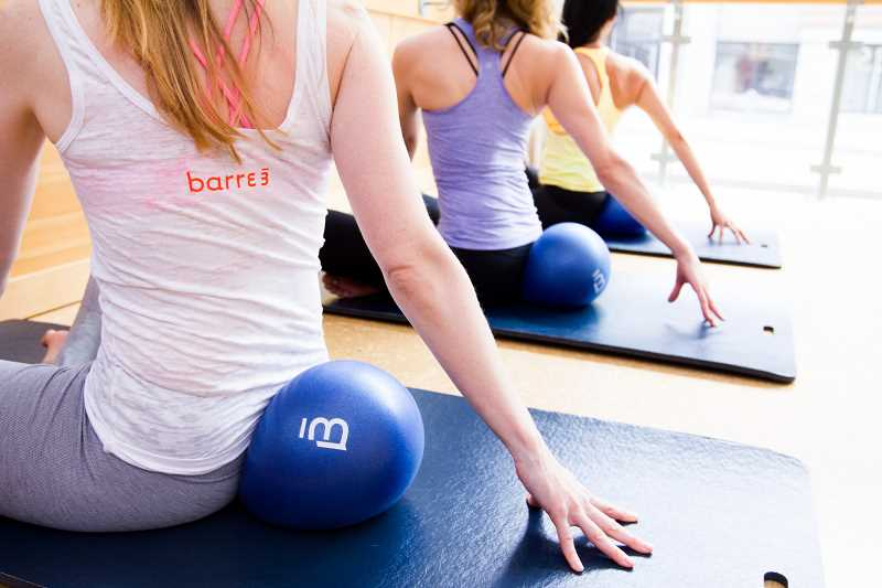 Class participants get a good stretch against a ball in a barre3 class.