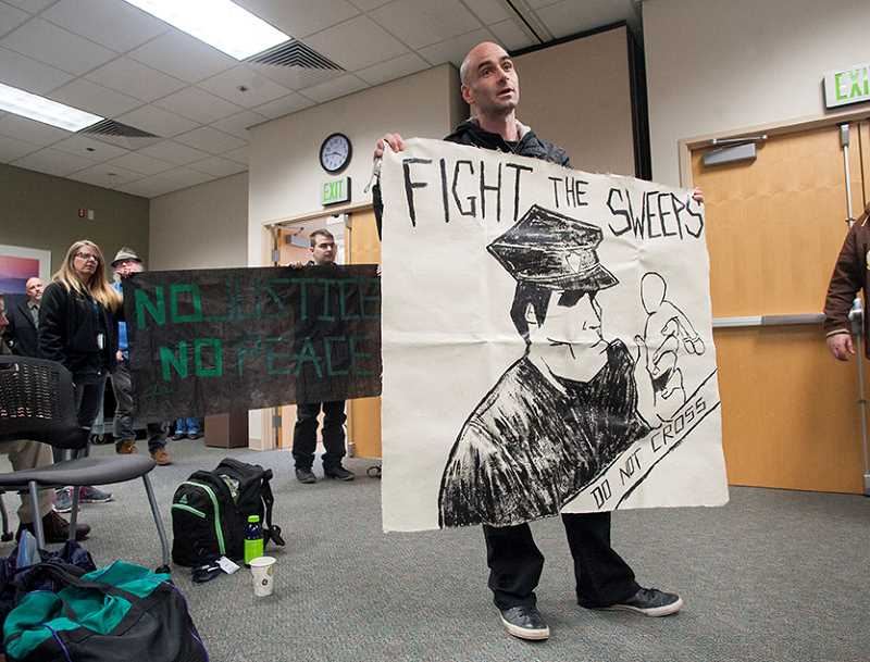 OUTLOOK PHOTO: JOSH KULLA - Homeless advocate and activist Kif Davis holds up a sign before the Gresham City Council Tuesday afternoon at city hall.