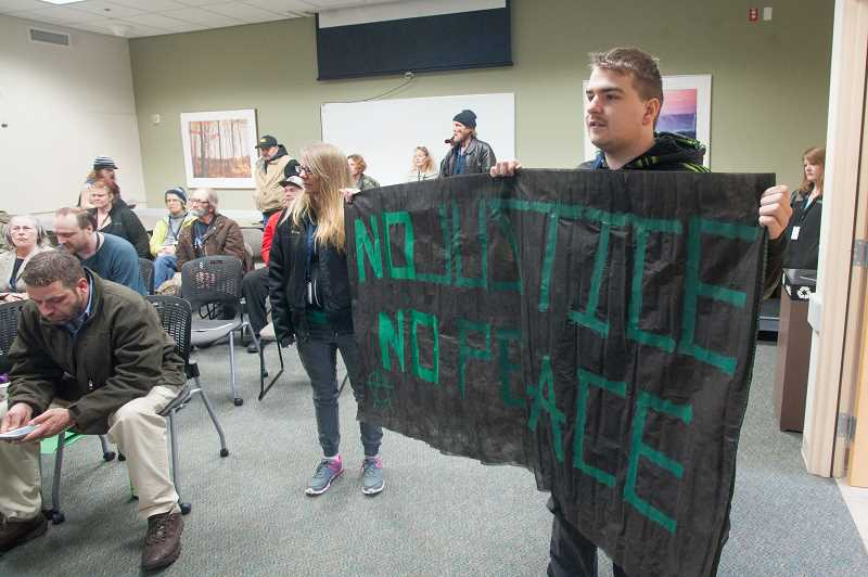 OUTLOOK PHOTO: JOSH KULLA - A young man who declined to give his name holds up a sign reading 'No justice, no peace,' Tuesday at a Gresham City Council meeting.