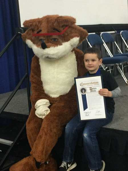 ESTACADA NEWS PHOTO: EMILY LINDSTRAND - After receiving the 911 Hero Medal of Honor award, seven-year-old Devin Duke takes a photo with Red E. Fox, the Association of Public Safety Communications Officials mascot.