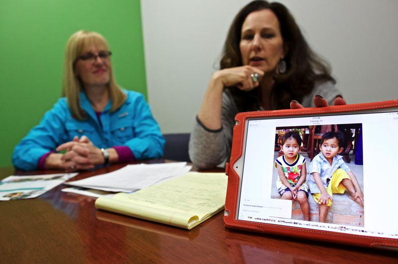 TIMES PHOTO: JAIME VALDEZ - Diana Burke, of Lake Oswego, watches as Annie Kubiak, of Beaverton, shows pictures of children from their visit to Cambodia.