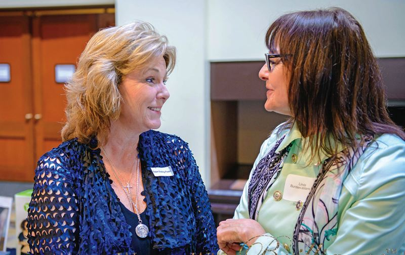 COURTESY OF WOMEN WITH BRILLANCE - Robin Posen, owner of the Beaverton-based Think Pink, a flamingo flocking services, chats with Linda Burden-Williams during a morning meeting of Women With Brilliance.