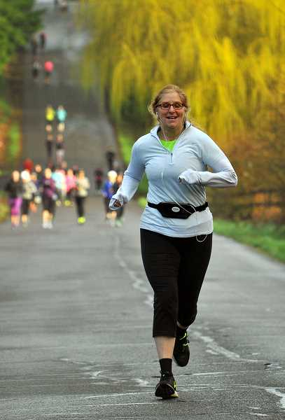 SPOKESMAN PHOTO: VERN UYETAKE - Jeri Bohard leads a group of runner and walkers as it heads down Rose Lane in Wilsonville.