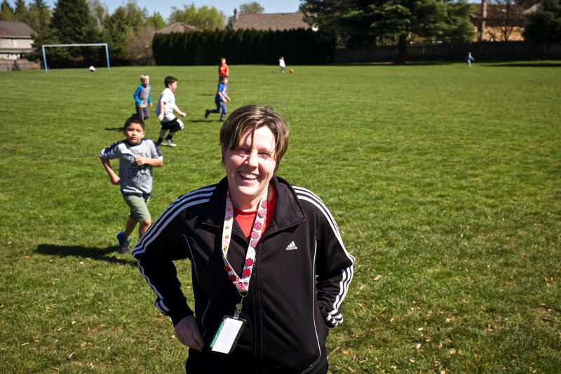 TIMES PHOTO: JAIME VALDEZ - Leah Findtner, a parent volunteer who heads the running club at Bridgeport Elementary School, stands where a track will be constructed on the soccer field behind the school.