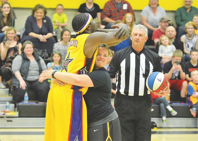 SPOTLIGHT PHOTO: JAKE MCNEAL - St. Helens High School Principal BG 'The Rock' Aguirre makes a chest pass against the Harlem Wizards on Monday at St. Helens High School.