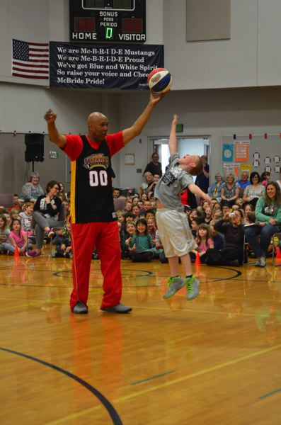 SPOTLIGHT PHOTO: NICOLE THILL - Levi Hileman, a third-grader at Lewis and Clark Elementary School, leaps to reach a basketball being held by 'Tojo' Henderson, a Harlem Wizards basketball player. Henderson visited three schools in St. Helens Monday afternoon, April 11.