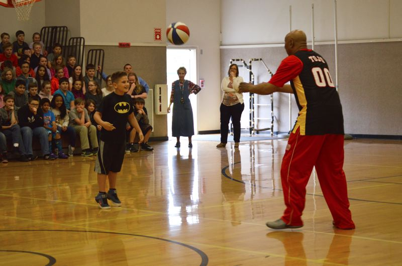 SPOTLIGHT PHOTO: NICOLE THILL - Cameron White, a fifth-grader at Lewis and Clark Elementary School, bounces a basketball off his head, imitating a trick performed by a Harlem Wizards basketball player during a school assembly Monday, April 11.